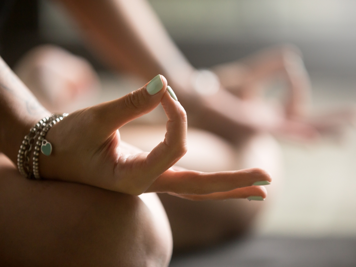 Gyan mudra close up, woman joining together the tip of index finger with thumb, wearing wrist bracelets, practicing yoga in concentration pose, stress relieve exercise at home, focus on right hand